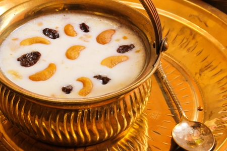 Indian Rice pudding payasam decorated with Cashews and raisin in a brass pot