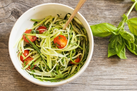 Zucchini pasta noodles with dressing in a white bowl