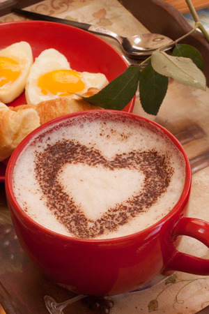 Coffee in red mug with hearth shape cocoa dust for valentines day