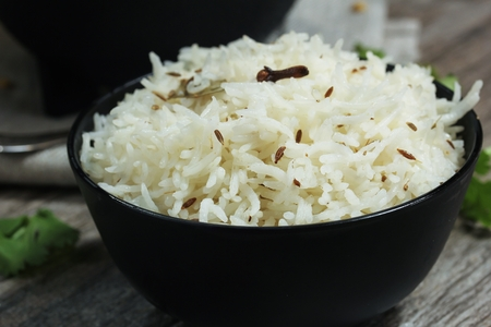 pices: Jeera Rice  Cumin Rice served in a black bowl, selective focus