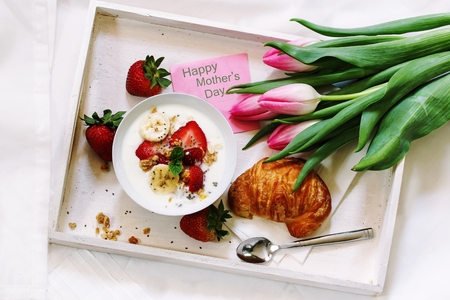 Breakfast yogurt bowl with strawberries and bananas served in a white tray with croissant Mothers day note and tulip flowers Stock Photo
