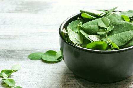 marango: Fresh Moringa leaves in a black bowl, selective focus Stock Photo