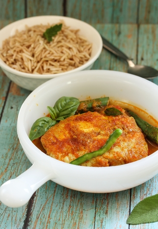 Assam Pedas fish curry  Fish cooked in sour and spicy gravy with tomatoes and okras, selective focus