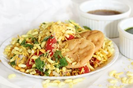 chaat: Bhel Puri -Popular Mubai street food served with coriander and tamarind chutney on white background, selective focus