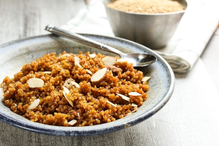 Lapsi  Broken wheat sweet pudding - Gujarati sweet dish made of Bulgur wheat palm sugar and Ghee fried nuts, selective focus