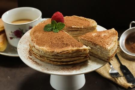 Tiramisu Crepe cake served on white cake stand- Multilayered Crepe cake with mascarpone cream filling, selective focus