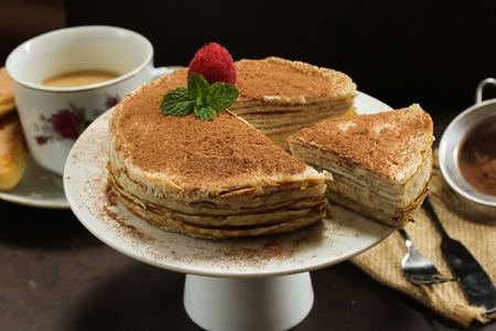 Tiramisu Crepe cake served on white cake stand- Multilayered Crepe cake with mascarpone cream filling, selective focus