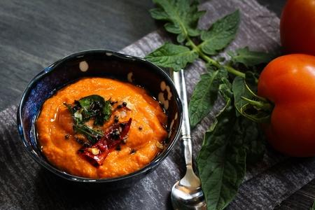 moody background: Tomato chutney  Spicy Tomato dip on dark moody background, selective focus