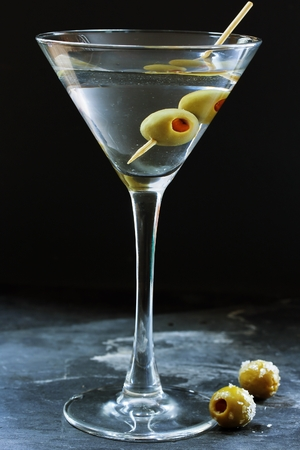 moody background: Vodka martini ccktail garnished with green olives on dark moody background, selective focus