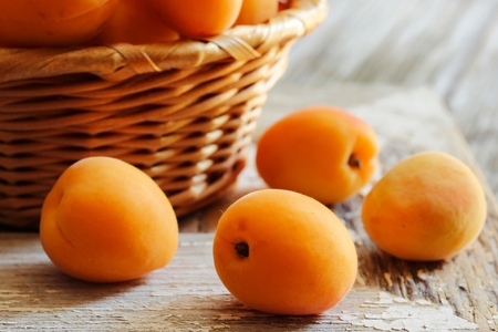 Fresh Apricots on bright wooden background, selective focus