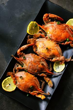 pincers: Steamed crabs with lemons on black platter