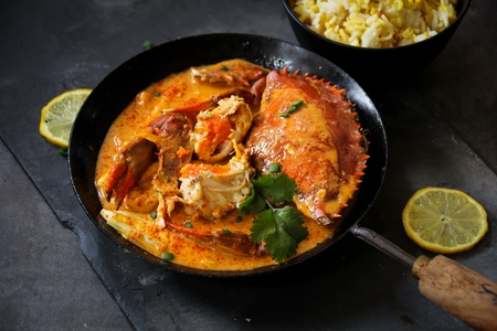 moody background: Crab curry in Thai infused red coconut curry sauce on dark moody background, selective focus