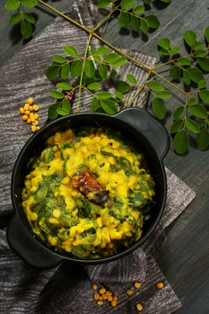 Lentil Moringa curry  Daal Drumstick leaves curry served in a black bowl