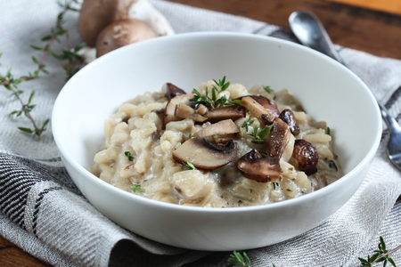 button mushroom: Bowl of Mushroom Risotto garnished with Thyme leaves, selective focus