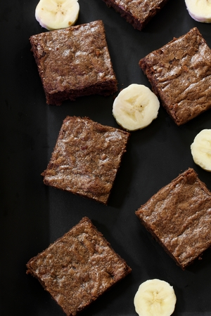 decadent: Banana chocolate brownies - Healthy Brownies using mashed bananas on dark black background, selective focus Stock Photo