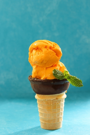 freezed: Homemade Mango Icecream in a cone against blue background , selective focus Stock Photo