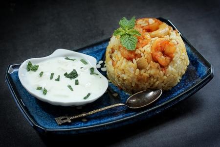 moody background: Shrimp Biryani  Prawn Biryani served with yogurt salad on dark moody background, selective focus Stock Photo