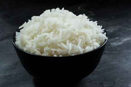 Basmati rice bowl, Cooked basmati rice in black bowl on dark moody background Stock Photo