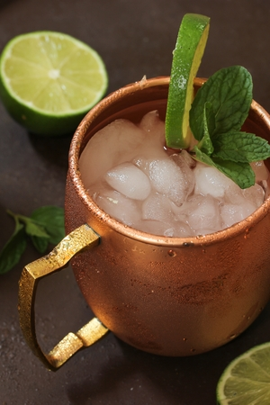 lemon wedge: Moscow Mule in a copper mug - Vodka drink served with mint garnish and lime wedge, selective focus
