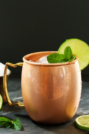 lemon wedge: Moscow Mule in a Copper Mug -Vodka drink served with mint garnished with a wedge of lime