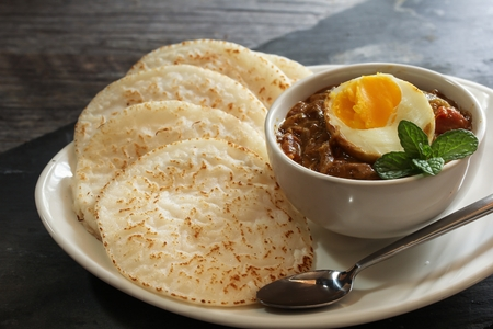 Appam and Egg masala  Rice pancake with egg curry - Popular South Indian  or Kerala breakfast Stock Photo