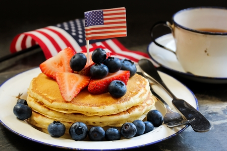 Stack of pancakes with USA flag and fresh berries, selective focus Фото со стока