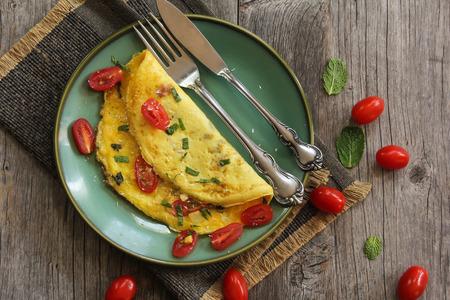 フォークとスプーン、セレクティブ フォーカス緑プレートにトマト オムレツ