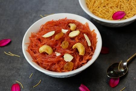 Vermicelli Kesari  Semiya Kesari - Indian sweet made of vermicelli ghee and nuts on dark moody background