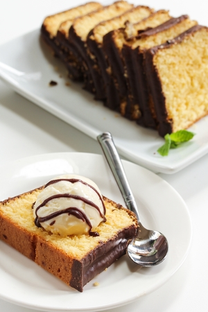 Piece of Pound cake with a dollop of icecream and chocolate drizzle, selective focus