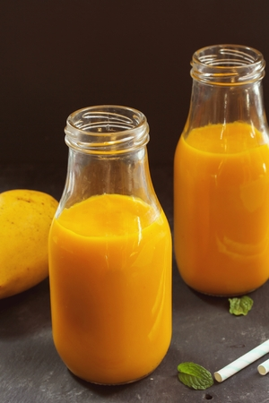 Mango Lassi or Mango smoothie in a glass jar, selective focus