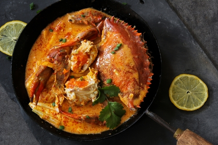 Crab curry in Thai infused red coconut curry sauce on dark moody background, selective focus