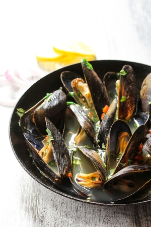 cilantro: Steamed Mussels in a white wine sauce on wooden background, selective focus