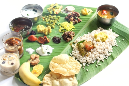 Onam feast on banana leaf isolated on white  South indian Vegetarian meal served in banana leaf, selective focus