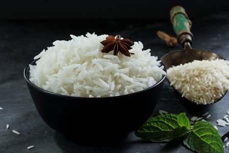 moody background: Basmati rice bowl, Cooked basmati rice in black bowl on dark moody background Stock Photo