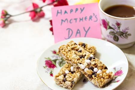 post it: Mothers Day background with granola bars coffee and Happay Mothers day note, selective focus Stock Photo