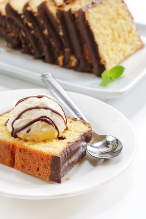 pound cake: Piece of Pound cake with a dollop of icecream and chocolate drizzle, selective focus