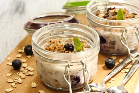 Overnight oats in a jar with blueberries and nuts, selective focus