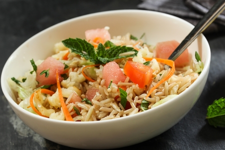 Rice salad  Healthy Brown rice salad with veggies and fruits served in a white bowl, selective focus