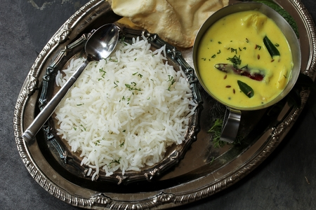 chick pea: Gujarati Kadhi served with rice and Papad - Indian vegetarian curry made of buttermilk and Chick pea flour Stock Photo