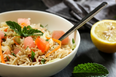 overs: Rice salad  Healthy Brown rice salad with veggies and fruits served in a white bowl, selective focus
