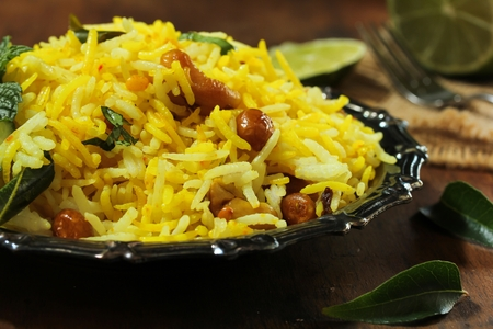 Lemon Rice - South Indian turmeric rice  garnished with nuts curry leaves and lemon juice, selective focus