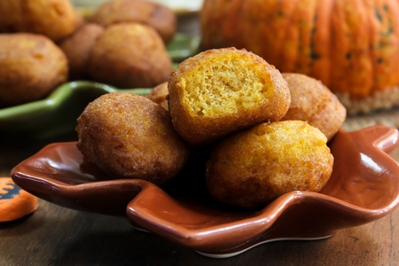 moody background: Homemade Pumpkin Fritters dusted with powdered sugar on dark moody background, selective focus