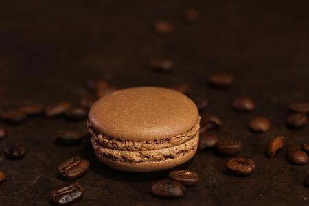 Chocolate Macaron / French macaron cookies on dark moody background, selective focus