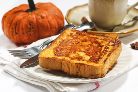 Homemade Pumpkin French toast  on Autumn background with pumpkin and pumpkin spice tea on side, selective focus