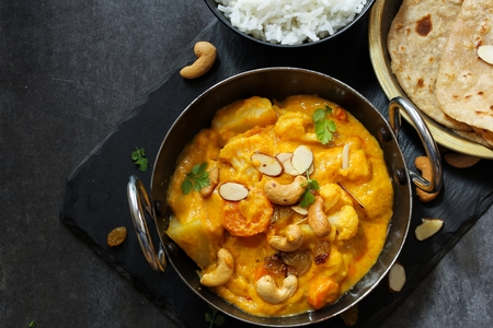 Vegetable or Navratan Korma - Indian Mixed Veg Curry served with bread and rice Stock Photo