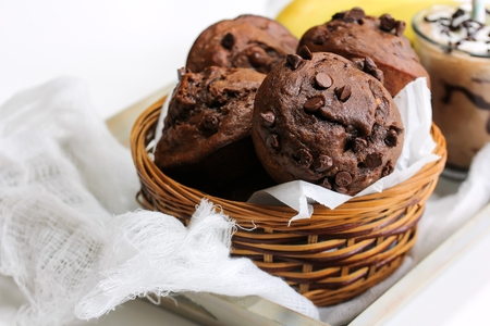 Homemade Banana chocolate chip muffins served in a basket, selective focus