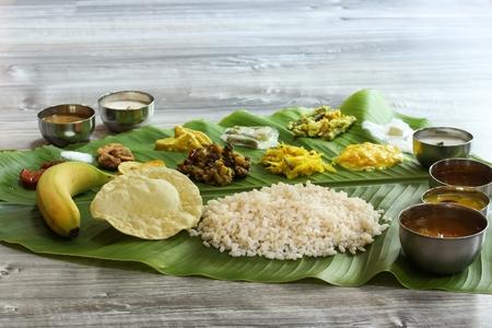 Tradicional Kerala Onam Sadya servido en Banana Leaf / comida vegetariana arroz al curry hervido y Papad servido durante festivales Foto de archivo