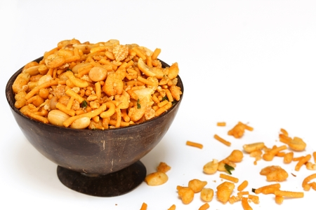 Mixture / Indian spicy snack mix served in coconut shell bowl on white background