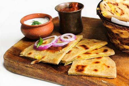 Aloo Paratha served in wooden board with raita and pickle against white background, selective focus