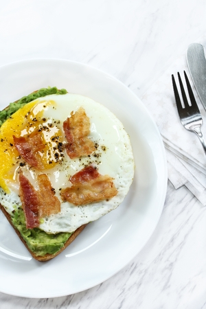 Avocado bread egg toast  topped with bacon and pepper, top down view